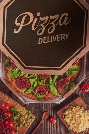 Brazilian pizza with tomato sauce, mozzarella, arugula, dried tomatoes and oregano in a delivery box (Pizza rucula with sun-dried tomatoes) - Top view.