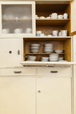 beige cupboard, open with cups and plates Stock Photo