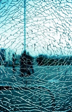 a window that is shattered with a green-blue background photo