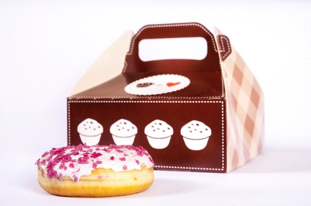 doughnut: isolated on white doughnut with pink sprinkles and a slightly out of focus wrapping box
