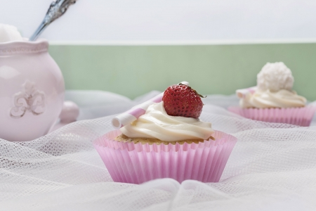 jam cupcake with mascarpone cream cheese topping strawberry on table in studio photo