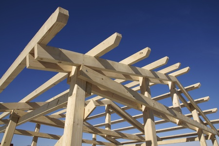 roof framework: Wooden roof during the early stages of construction in a sunny day Stock Photo