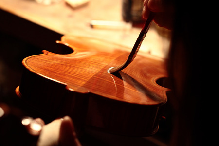 violin making: Final touch. An Italian Violinmaker who paints a violin she created in a neapolitan workshops Stock Photo