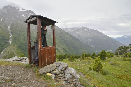 hiker with cell phone in a mountain phone booth Stockfoto