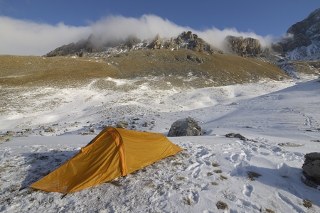 bivouac: One orange tent in the mountains.