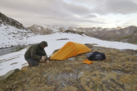 bivouac: A man assembles an orange tunnel tent in the Italian Alps. Stock Photo