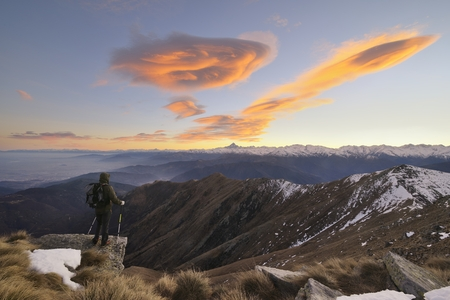 lenticular: Hiker with backpacking Observes the Alps under a spectacular sky with lenticular clouds.