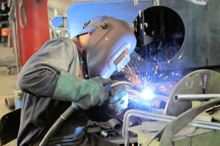 erecting: worker with protective mask welding metal