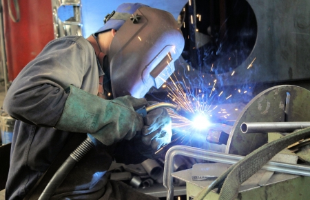 mag: worker with protective mask welding metal
