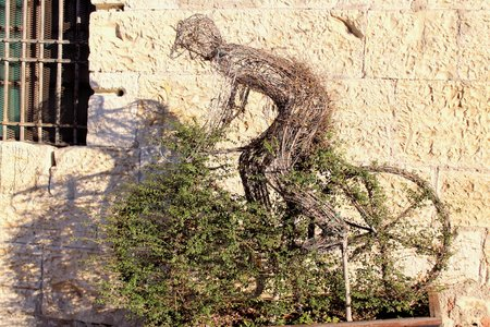 sculpted: Carved figure of a cyclist in a bush with topiary