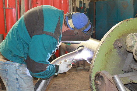 mag: Welder with protective mask welding metal