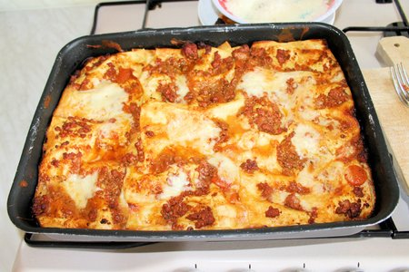 Baked lasagna in metal container from the oven photo