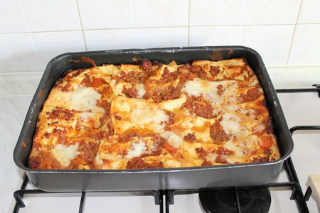 Baked lasagna in metal container from the oven Reklamní fotografie