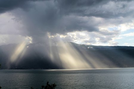 Sun rays through the clouds on Garda lake photo