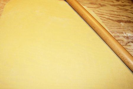dough being flattened on a wooden cutting board photo