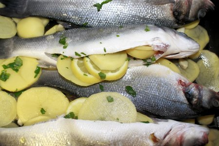 seabass: Raw seabass fish with parsley filled with potatoes and lemon ready for the oven