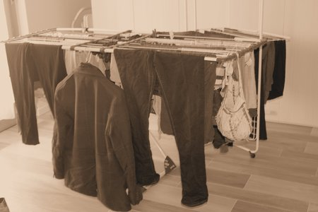 clothes hanging: clotheshorse with different clothes hanging Stock Photo