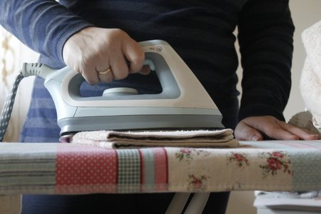 ironing board: Ironing a towel with a steam iron on an ironing board