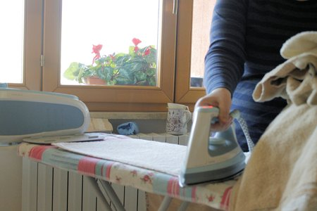 steam iron: Ironing a towel with a steam iron on an ironing board
