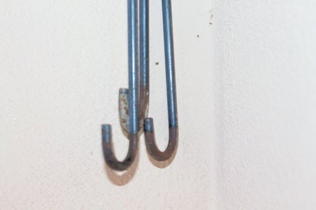 structuring: iron hooks on white wall