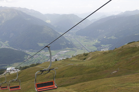 Chairlift ski lift in the european Alps. Transporting hikers in summer season.