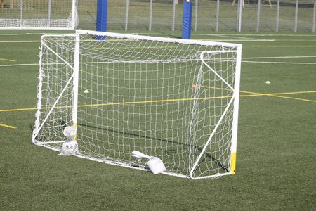 Part of soccer goal door with white net. Close up for football goal at soccer field with green grass and sport stadium, white line and soccer field corner. Sports elements, equipment and environment.