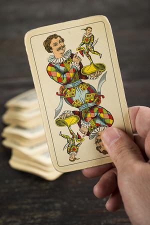 wildcard: hand holding a joker catch from the deck