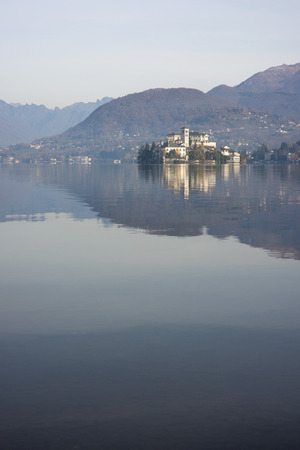 orta: Orta lake and San Giulio island in a misty morning of novenber Stock Photo