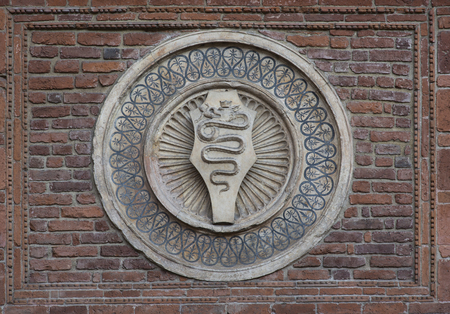 crown spire: The snake eats a man, the symbol of milan on a wall of Church of Holy Mary of Grace (Chiesa di Santa Maria delle Grazie, 1497), Milan, Italy Editorial