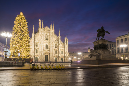 Milan, Italy: Cathedral square in december with Christmas tree in front of Milan cathedral, night view. A row of yellow sharing bicycles in the foreground.