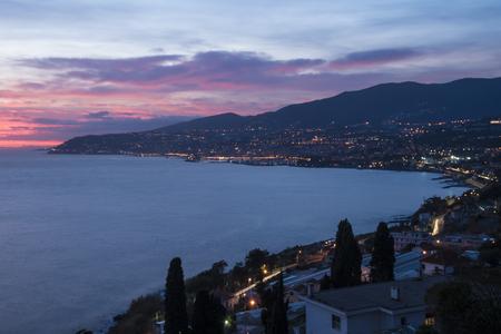 백그라운드에서 산 레모의 도시와 이탈리아 해안의 밤 파노라마. 스톡 콘텐츠