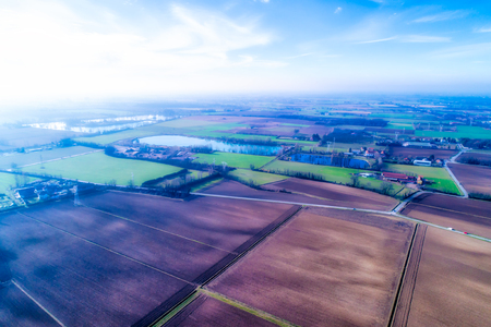 Plowed fields and ponds in the Po Valley, Italy. Aerial view in a foggy morning.