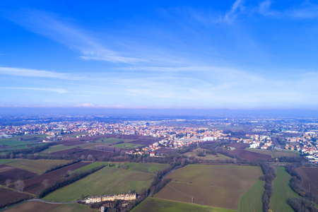 Fields and towns around Milan in the Po Valley, Italy. Aerial view. In the background the Italian Alps with Monte Rosa.