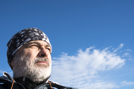 Portrait of mature sporty man with beard, sky background. Stock Photo