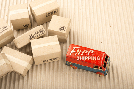 Free shipping van, vintage toy truck with cardboard boxes. Delivery concept.