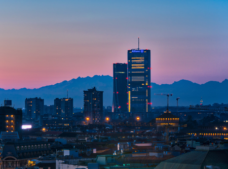 Milan, Italy - January 13, 2018: The new skyscrapers in CityLife district and the Monte Rosa mountain on the background. Sunset view.
