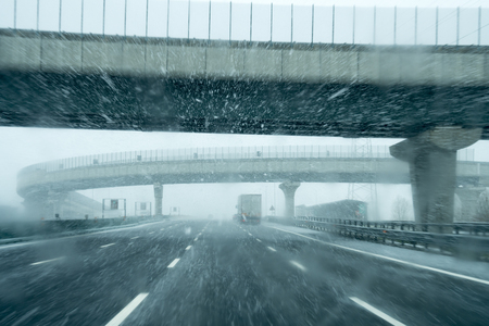 Snowfall on the highway, driving in bad weather.
