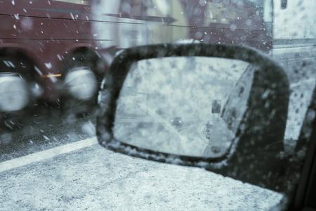 Winter driving, rear car mirror during a snowfall. Stok Fotoğraf