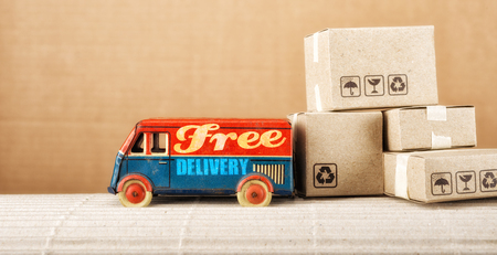 Free delivery van, vintage toy truck with cardboard boxes. Shipping concept. Stock Photo
