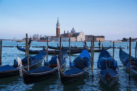 Venice, Italy - March 23, 2018: moored gondolas and the San Giorgio Maggiore church.