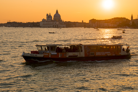 Venice, Italy - March 23, 2018: A typical public transport boat named Vaporetto, sails in the lagoon at sunset. The church of Santa Maria della Salute in the background.