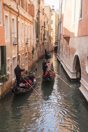 Venice, Italy - March 23, 2018: three gondolas in a narrow canal