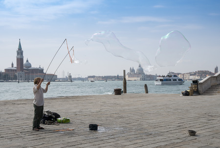 Venice, Italy - March 23, 2018: a street artist creates big soap bubbles on the waterfront promenade named Riva degli Schiavoni.