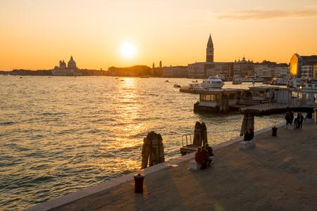 Venice, Italy - March 23, 2018: cityscape at sunset from the waterfront promenade named Riva degli Schiavoni. 新聞圖片