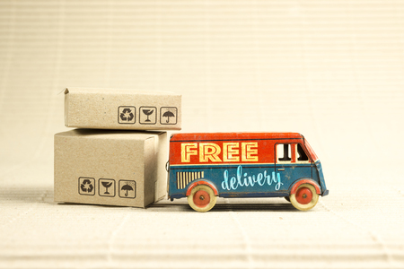Free delivery van, vintage toy truck with cardboard boxes. Shipping concept. Foto de archivo