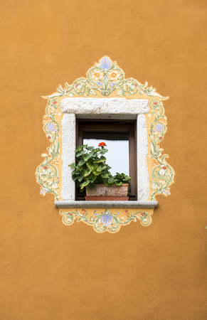 Window with floral decorations on an ancient house