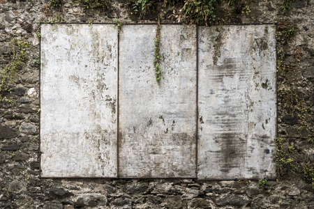 Old blank billboard on stone wall, space for copy text. 版權商用圖片