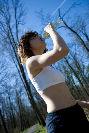 young woman drinking after a jogging session photo