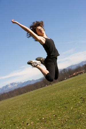 Oblique view of a young adult making a jump in a park photo