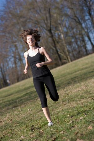 Full figure of a young woman running in a park with an oblique view photo
